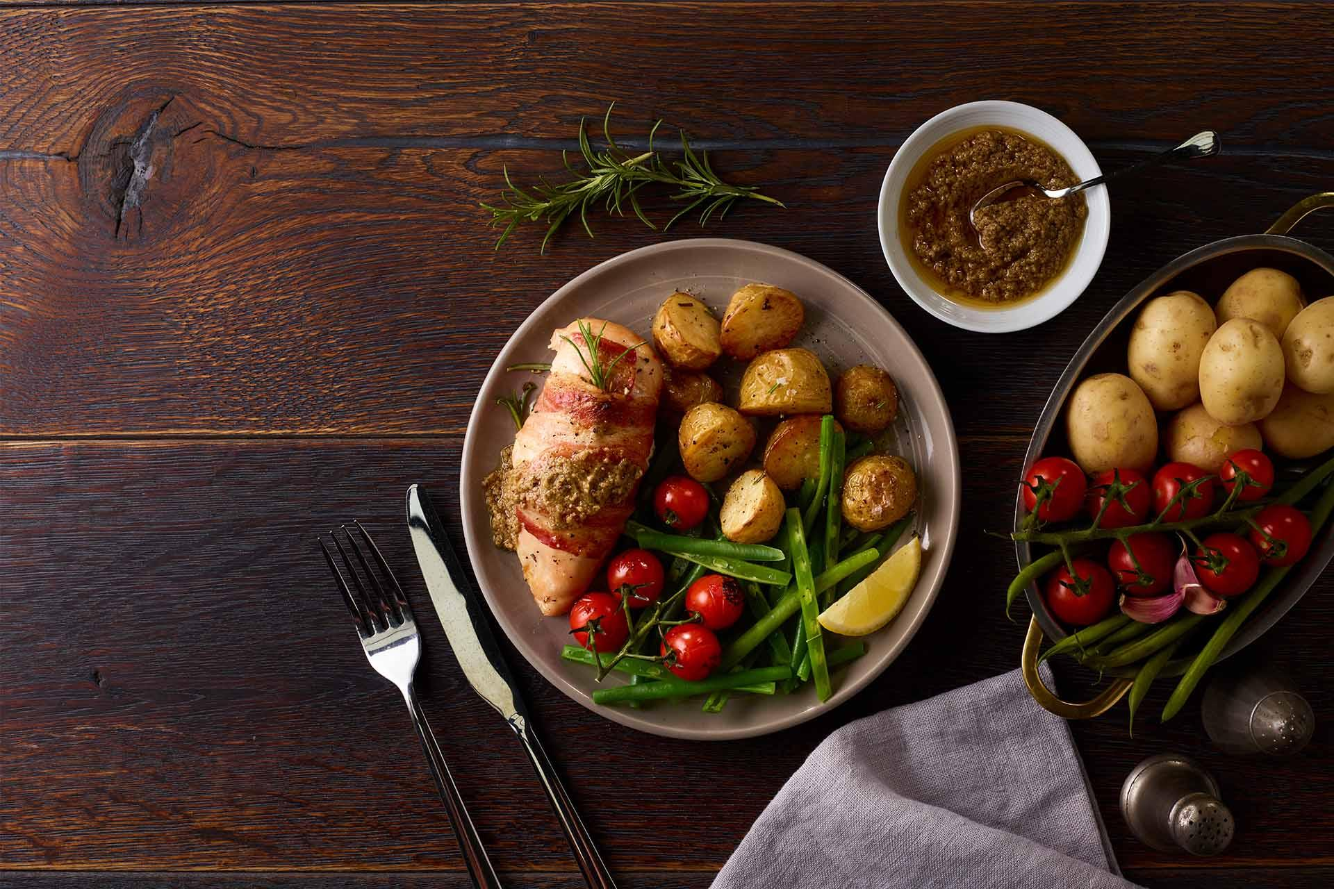 Chicken wrapped in bacon with rosemary, lemon and new potatoes